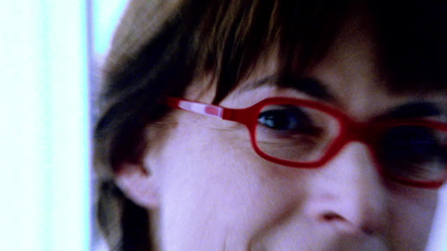 OVEREXPOSED close up PORTRAIT woman with red eyeglasses half-smiling / zoom in eye