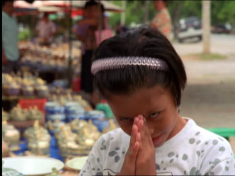 close up portrait young asian girl smiling + bowing to camera / thailand - respect点の映像素材/bロール