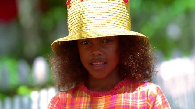 close up portrait young black girl wearing straw hat smiling + holding globe outdoors / florida - straw hat stock videos & royalty-free footage