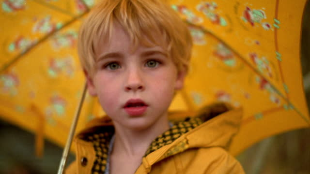 close up portrait young blonde girl under umbrella turning to camera and smiling outdoors / nova scotia - raincoat stock videos & royalty-free footage
