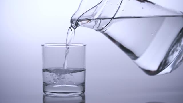 vidéos et rushes de 4k fermer vers le haut de verser de l'eau potable dans le verre, studio tourné - bouteille d'eau minérale