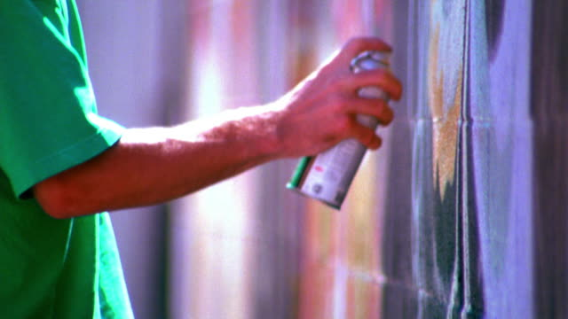 close up profile arms of two young men spraypainting on wall / los angeles - graffiti stock videos & royalty-free footage