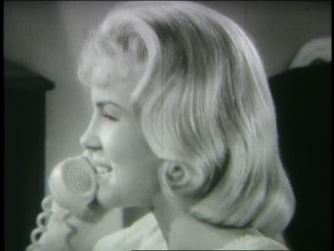 b/w 1962 close up profile blond teenage girl talking on telephone - 1962年点の映像素材/bロール