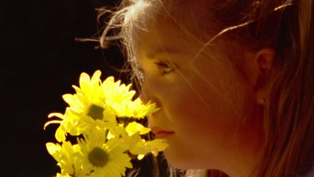 close up profile blonde girl holding bouquet of yellow flowers + smelling them outdoors - one girl only stock videos & royalty-free footage