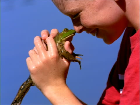 close up PROFILE boy holding frog, rubbing it on his nose + smiling outdoors