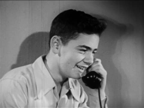 b/w 1949 close up profile boy talking on telephone / educational - one teenage boy only stock videos & royalty-free footage