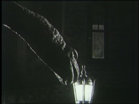 vidéos et rushes de b/w 1925 close up profile brontosaurus roars at lamp in london at night - 1925