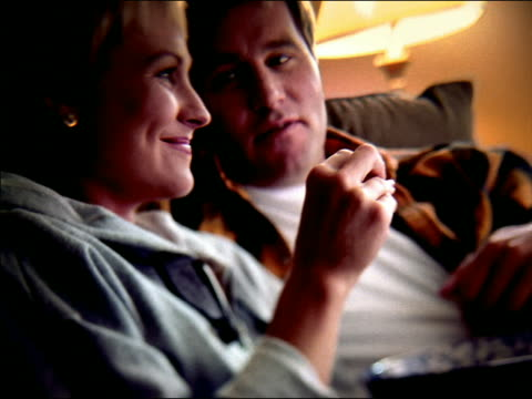 overexposed close up profile couple sitting on sofa watching television, laughing + talking - overexposed stock videos & royalty-free footage
