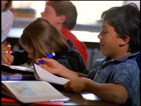 close up profile dark-haired boy with blue magic marker sitting next to boy + girl in classroom - skolmaterial bildbanksvideor och videomaterial från bakom kulisserna