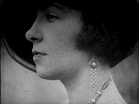 stockvideo's en b-roll-footage met b/w 1925 close up profile face of woman in hat with drop earrings / newsreel - oorbel