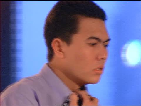 close up PROFILE frustrated Indonesian businessman loosening tie / Jakarta