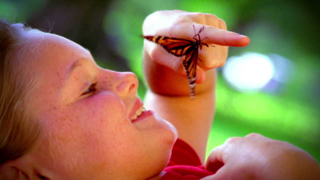 close up profile girl with freckles lying on back looking at monarch butterfly on finger outdoors - freckle stock videos & royalty-free footage