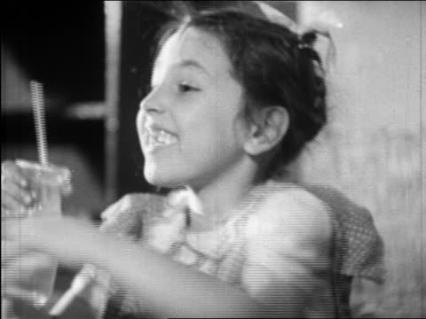 vidéos et rushes de b/w 1945 close up profile girl with straw in drink talking + smiling / educational - seulement des petites filles