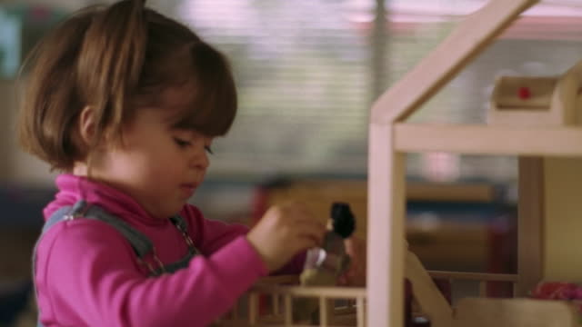close up profile hispanic female toddler playing with dollhouse - dollhouse stock videos & royalty-free footage