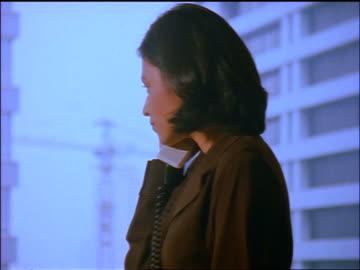 vídeos y material grabado en eventos de stock de close up profile indonesian businesswoman talking on telephone indoors + smiling / jakarta - teléfono con cable