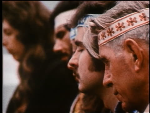 1970 close up PROFILE line of people in headbands rolling heads with eyes closed / PAN to guru leading them