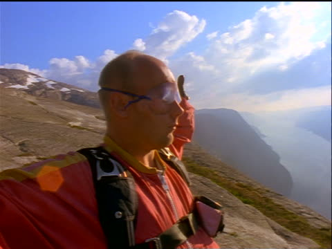 close up PROFILE male base jumper wearing goggles + coveralls stretching on edge of cliff / Sweden
