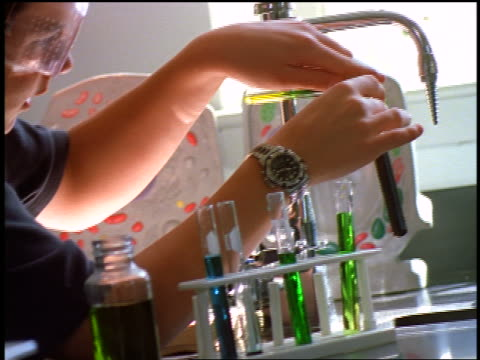 stockvideo's en b-roll-footage met canted close up profile male student pouring liquid from test tubes into test tube in laboratory - alleen één tienerjongen