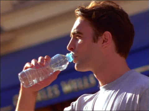close up profile man standing outside wearing t-shirt drinking water from clear plastic bottle / france - t shirt stock videos and b-roll footage