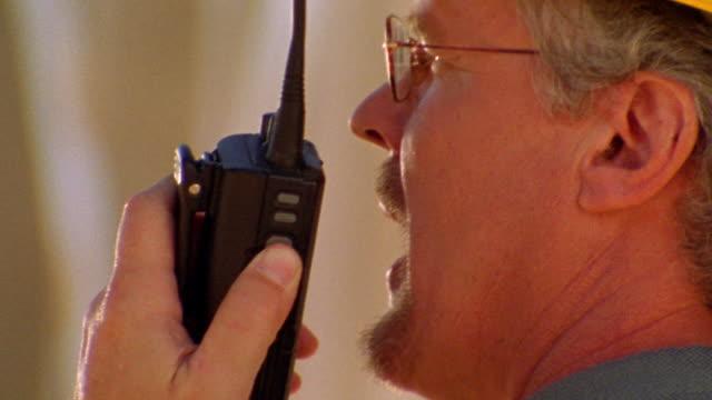 vídeos y material grabado en eventos de stock de close up profile man with hard hat + eyeglasses talking on walkie talkie - walkie talkie