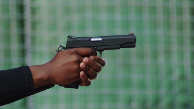 Close up profile of a semi-automatic pistol held by a black man's hands and fired multiple times on a shooting range; spent cartridges fly into the air.