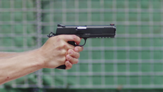 Close up profile of a semi-automatic pistol held by a white man's hands is fired on a shooting range; spent cartridges fly into the air.