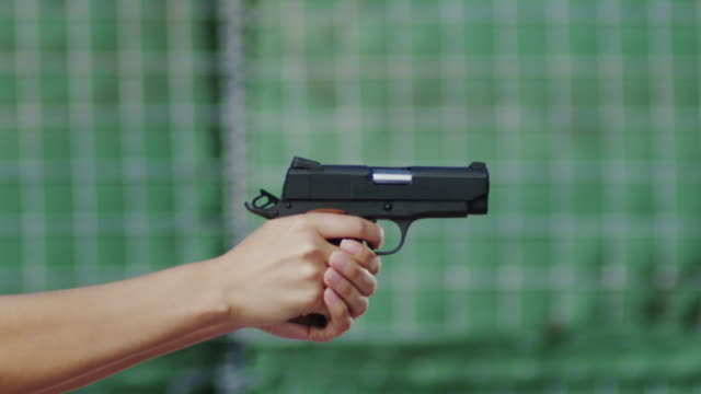 Close up profile of a semi-automatic pistol held by a woman's hands and fired multiple times on a shooting range; spent cartridges fly into the air.
