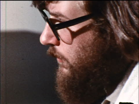 1973 close up profile of bearded, long-haired man in eyeglasses indoors / industrial - profile stock-videos und b-roll-filmmaterial