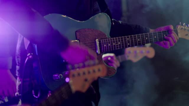 vidéos et rushes de close up profile of guitar strumming on stage - musicien
