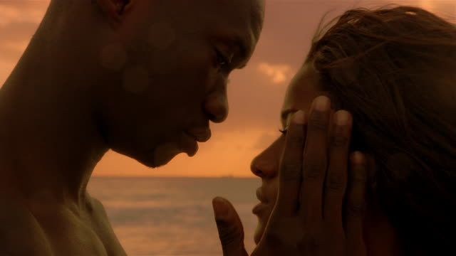 close up profile of man and woman kissing with ocean in the background - afrikanischer abstammung stock-videos und b-roll-filmmaterial