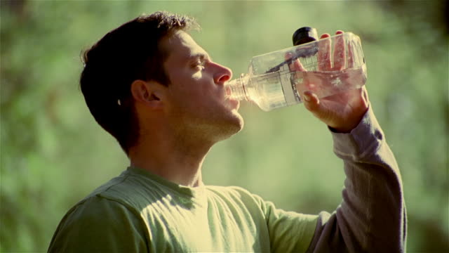 vídeos y material grabado en eventos de stock de close up profile of man drinking water from water bottle - sediento