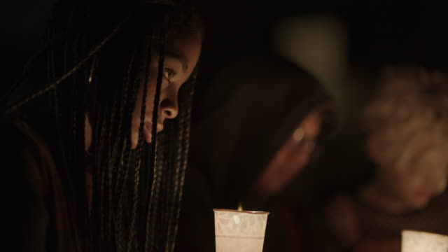 close up profile of sad girl at candlelight vigil at night / provo, utah, united states - trauernder stock-videos und b-roll-filmmaterial