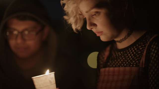 close up profile of sad girl at candlelight vigil at night / provo, utah, united states - aktivist stock-videos und b-roll-filmmaterial