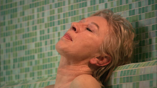 close up profile of woman in sauna with head back/ pan length of woman's body - profile stock videos and b-roll footage