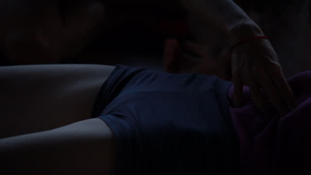 close up profile of woman, slightly lit, natural light, mostly silhouetted, in yoga attire,as the camera pans down her body we see a hand pushing into her stomach area, as the camera continues to pan down to her shins well she is lying on a hardwood floor - kelly mason videos stock videos & royalty-free footage
