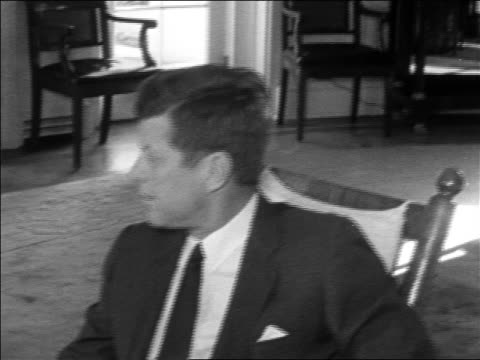 vídeos de stock, filmes e b-roll de b/w 1962 close up profile president john kennedy sitting in chair talking to someone in white house - 1962