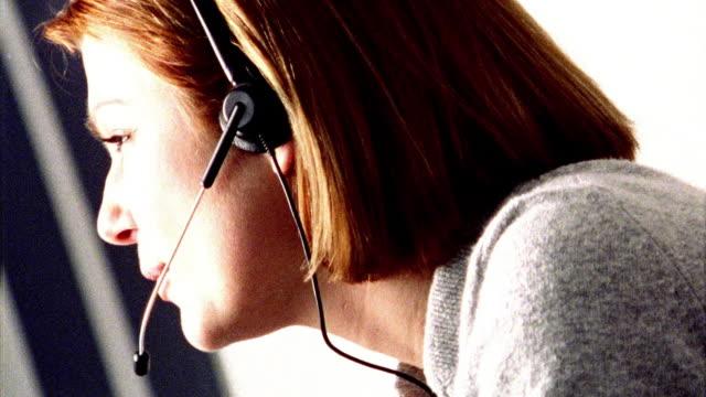 OVEREXPOSED close up PROFILE redhead woman wearing headset talking + smiling / turning head toward camera