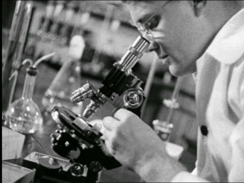 b/w 1940 close up profile scientist looking thru microscope in laboratory / industrial - 1940 stock videos & royalty-free footage
