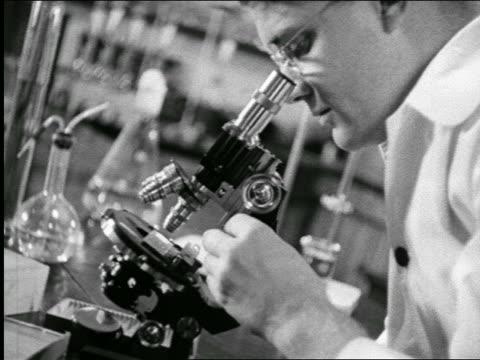 stockvideo's en b-roll-footage met b/w 1940 close up profile scientist looking thru microscope in laboratory / industrial - 1940