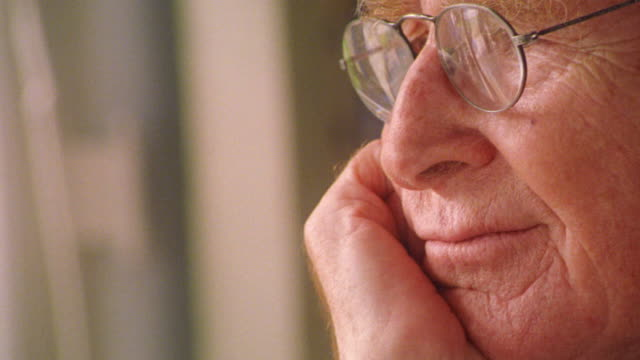 close up PROFILE senior man in eyeglasses resting chin on hand looking somber