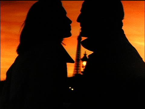 close up profile silhouette of couple kissing at sunset / eiffel tower in background / paris - vuxen bildbanksvideor och videomaterial från bakom kulisserna