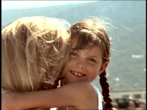 vidéos et rushes de close up profile small girl hugs woman outdoors / woman sticks tongue out at camera / corsica - langue humaine