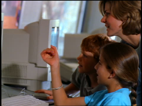 close up profile teacher + two students pointing to computer screen in classroom - profile stock-videos und b-roll-filmmaterial