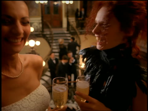 Close up profile two women in formalwear talk and hold champagne with people ascending ornate staircase in background