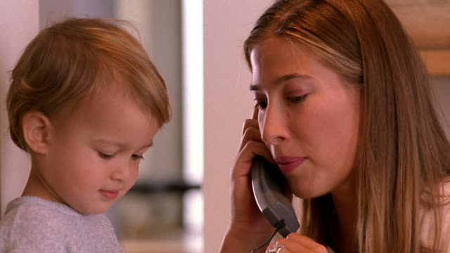 close up profile woman talking + passing telephone to girl toddler - landline phone stock videos & royalty-free footage