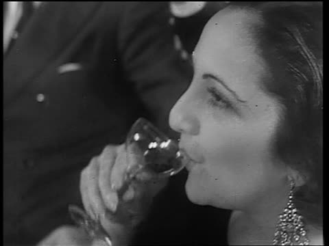 b/w 1933 close up profile woman with large earrings drinking from small glass / end of prohibition - 1933年点の映像素材/bロール