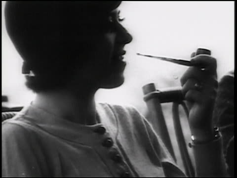 b/w 1938 close up profile women in hat sitting + smoking pipe / newsreel - 1938 stock videos and b-roll footage