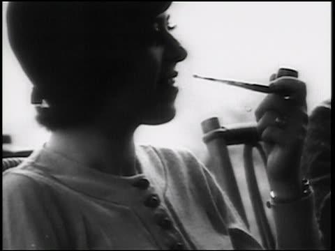 B/W 1938 close up PROFILE women in hat sitting + smoking pipe / newsreel