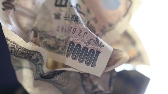 Close Up pull focus from Japanese 10000 yen right to a US 100 dollar banknote arranged for video in Tokyo Japan on Monday June 20 Close Up crunched...