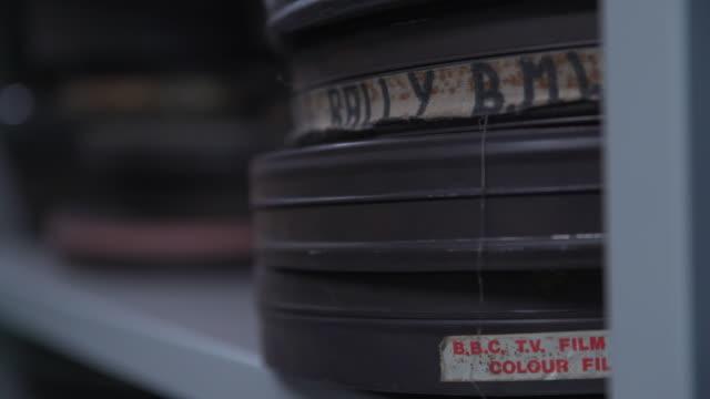 close up pull focus on stacks on metal film cans on a shelving unit - bbc news bildbanksvideor och videomaterial från bakom kulisserna